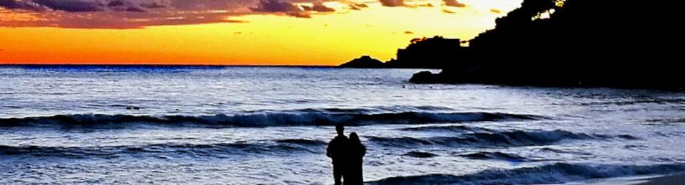 Paar schaut Sonnenuntergang am Meer
